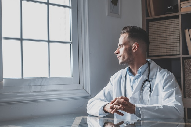 Zamyślony młody mężczyzna kaukaski lekarz w białym mundurze medycznym wygląda na myślenie lub rozmyślanie na odległość okna, poważny mężczyzna lekarz ogólny planuje przyszłą karierę lub sukces w medycynie, wizualizuje pisanie w miejscu pracy