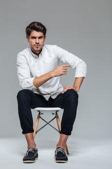 Zamyślony młody mężczyzna z włosami, siedzący na krześle i wskazujący palcem, odizolowany na szarej ścianie