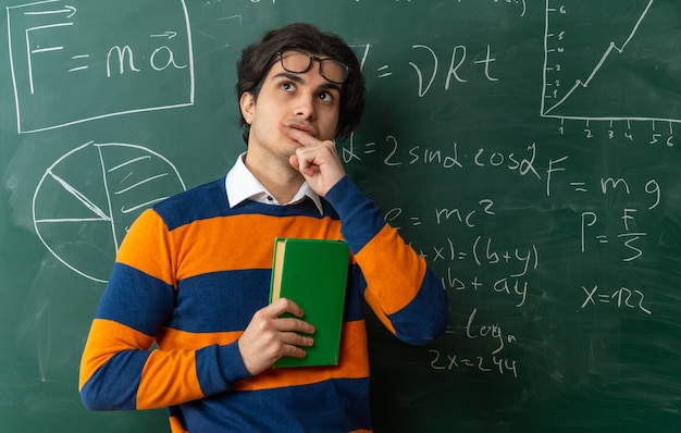 Zamyślony młody nauczyciel geometrii w okularach na czole stojący przed tablicą w klasie trzymający zamkniętą książkę dotykającą wargi patrzącą w górę