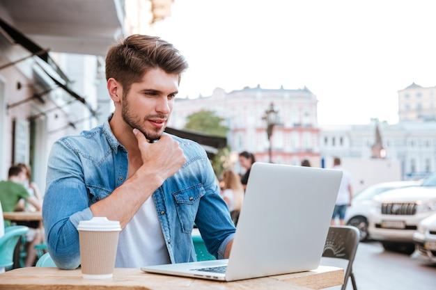 Zamyślony młody przypadkowy mężczyzna patrzący na laptopa siedząc w kawiarni na świeżym powietrzu