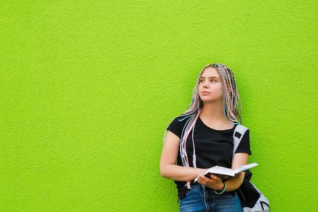Zamyślony młody student na zielono