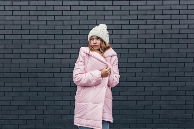 Zamyślony model w zimowe ubrania pozowanie w zimny dzień. czarujący kaukaski kobieta w kapeluszu stojącym na szarym murem.
