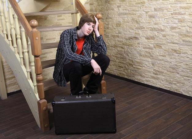 Zamyślony nastolatek, 14 lat, w koszuli w kratę, smutny siedzi na stopniach drewnianych kręconych schodów obok brązowej walizki.
