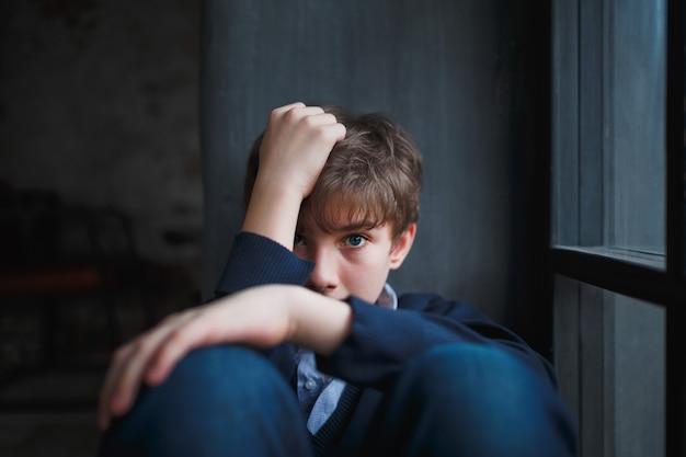 Zamyślony nastolatek smutny chłopiec w niebieskiej koszuli i dżinsach siedzi przy oknie i zamyka twarz rękami.