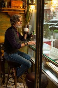 Zamyślony nastrój. przemyślany przystojny mężczyzna siedzi przy stoliku kawiarnianym, pijąc kawę i patrząc przez okno na przechodzących ludzi.