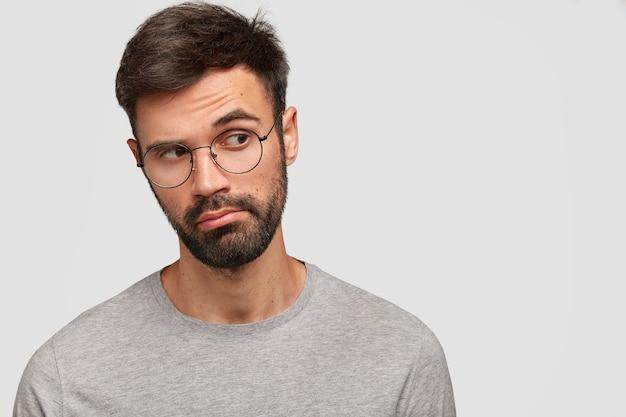 Zamyślony, nieogolony atrakcyjny mężczyzna wygląda w zamyśleniu na bok, ma głębokie myśli, ma okrągłe okulary, pozuje na białej ścianie