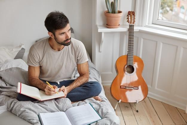 Zamyślony nieogolony mężczyzna siedzi w pozie lotosu na łóżku