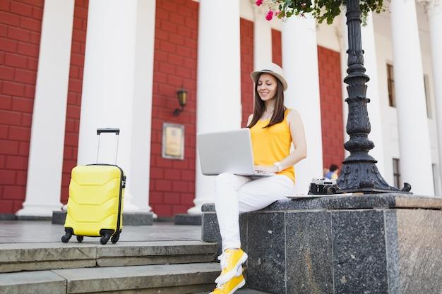 Zamyślony podróżnik turysta kobieta w ubraniach casual, kapelusz z walizką siedzi za pomocą pracy na komputerze typu laptop w mieście na świeżym powietrzu. dziewczyna wyjeżdża za granicę na weekendowy wypad. styl życia podróży turystycznej.