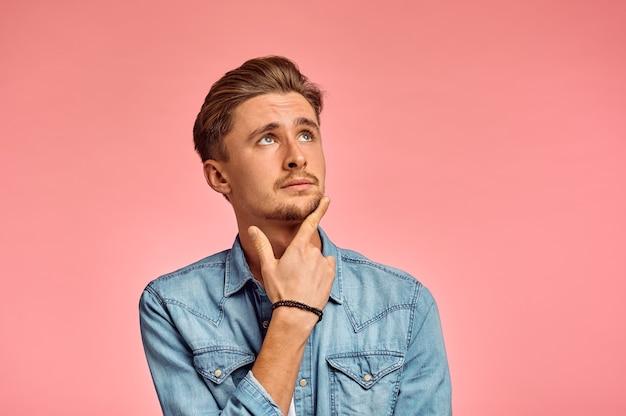Zamyślony portret mężczyzny, różowe tło, emocje