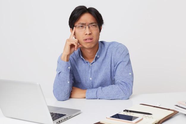 Zamyślony poważny azjatycki młody biznesmen w okularach siedzi w miejscu pracy z laptopa i myślenia na białym tle nad białą ścianą