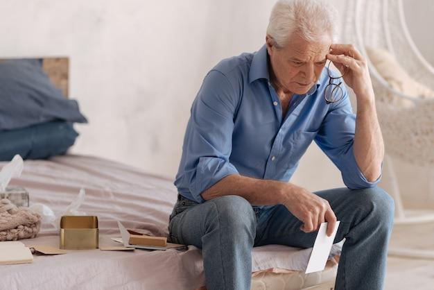 Zamyślony, przygnębiony nieszczęśliwy mężczyzna trzymający list i dotykający głowy, będąc zaangażowanym w swoje wspomnienia