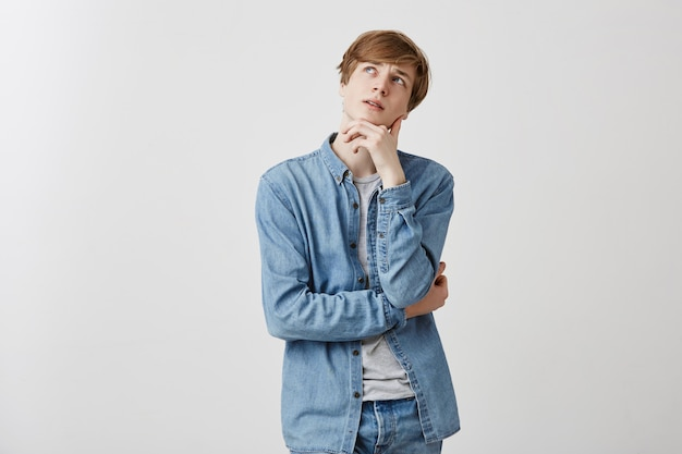 Zamyślony, przyjemnie wyglądający młody mężczyzna o jasnych włosach i niebieskich oczach w dżinsach, trzyma rękę pod brodą, patrzy w zamyśleniu, próbuje zebrać myśli, marzy o wakacjach za granicą lub samochodzie