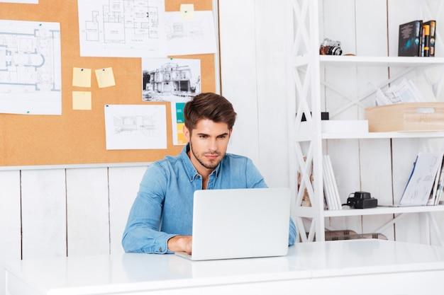 Zamyślony przystojny brodaty biznesmen dorywczo siedzący z laptopem w biurze