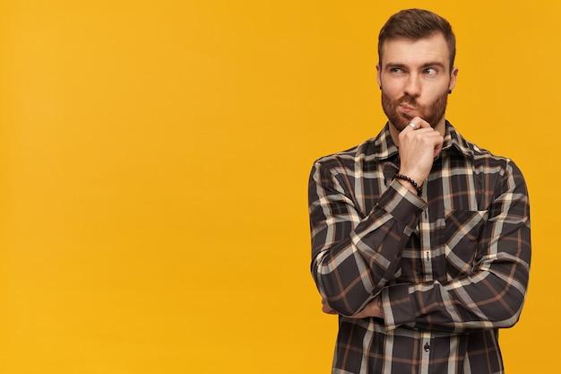 Zamyślony przystojny młody brodaty mężczyzna w kraciastej koszuli dotyka jego brody i myśli nad żółtą ścianą patrząc w bok