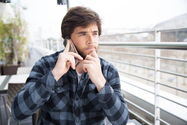 Zamyślony, skoncentrowany młody człowiek myśli ciężko