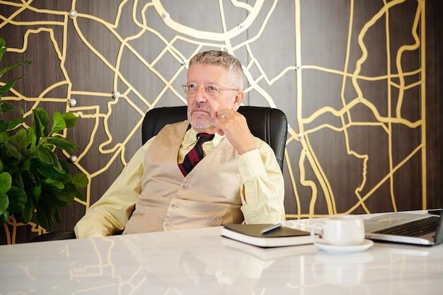 Zamyślony starszy przedsiębiorca siedzi przy stole w biurze z otwartym laptopem i filiżanką kawy
