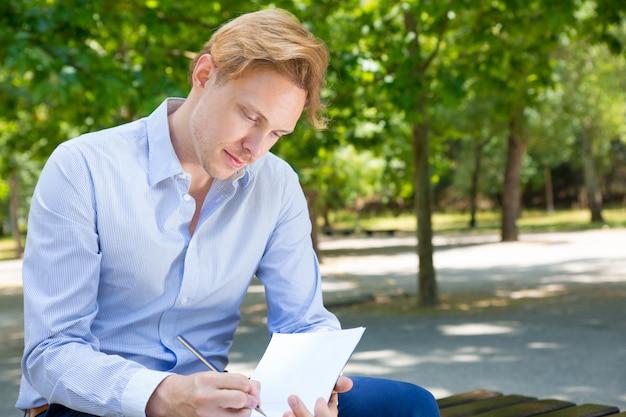 Zamyślony student koncentruje się na notatkach