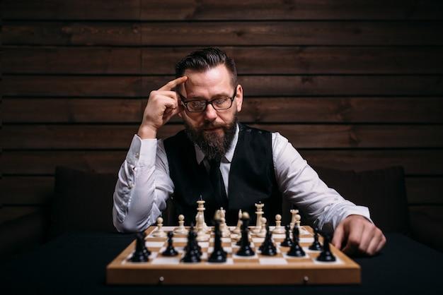 Zamyślony szachista myśli o strategii gry