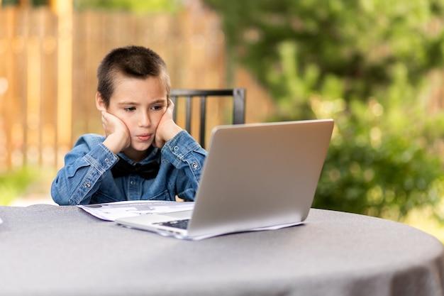 Zamyślony uczeń chłopiec jest zaangażowany w lekcje przez laptopa w domu w ogrodzie. zajęcia online dla dzieci. uczeń słucha wykładu i rozwiązuje problemy