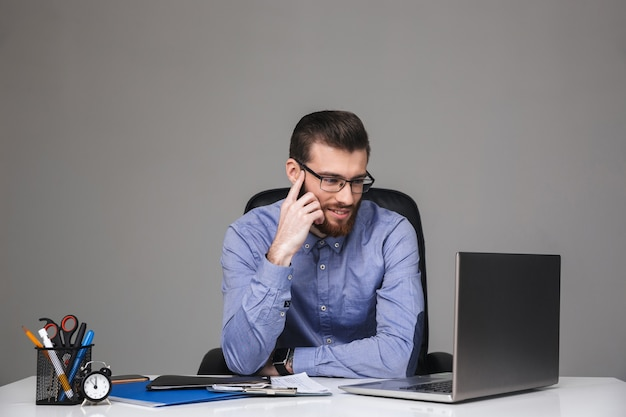 Zamyślony uśmiechnięty brodaty elegancki mężczyzna w okularach korzystający z laptopa siedząc przy stole w biurze