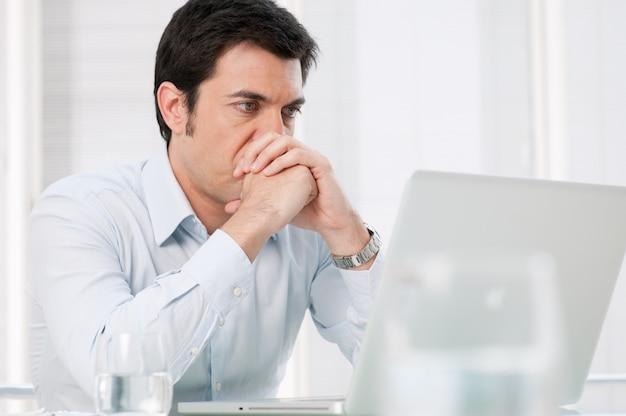 Zamyślony zaabsorbowany biznesmen ogląda na laptopie komputer z zmartwioną miną