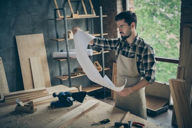 Zamyślony, zamyślony, zainteresowany mężczyzna trzymający kartkę papieru z planami otoczoną opiłkami i narzędziami