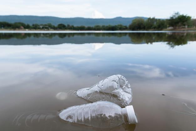 Zanieczyszczenia butelek z wodą w rzece. plastikowe śmieci w wodzie. zanieczyszczenie środowiska .