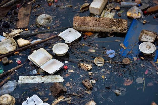 Zanieczyszczenia na plaży. plastikowe butelki i inne śmieci na rzece.