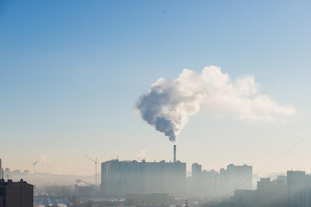 Zanieczyszczenia nad miastem w mroźny poranek, pojęcie ekologii. jasne błękitne niebo i dym. fabryczna rura w pochmurne niebo. miejski widok przemysłowy z ptakami.