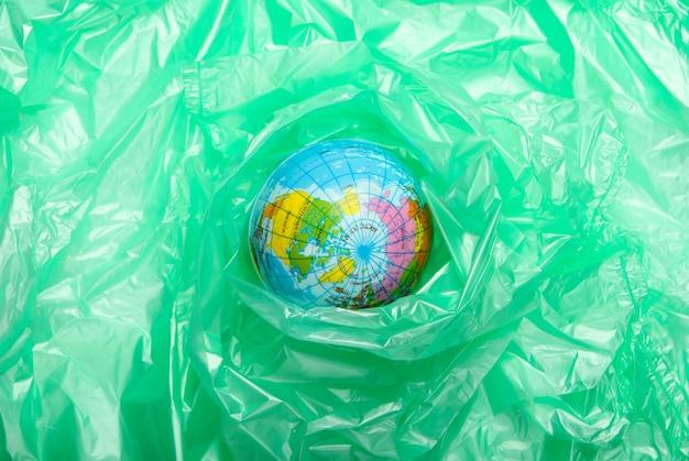 Zanieczyszczenia. nie zawiera plastiku. koncepcja eco. kula ziemska zapakowana w plastikową torbę. uratuj planetę. minimalizm