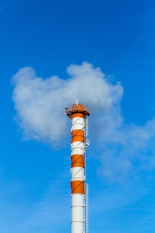 Zanieczyszczenie dymem rury dymne na tle błękitnego nieba