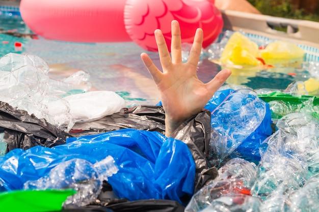 Zanieczyszczenie plastikiem i problem środowiskowy, ręka człowieka w plastikowym morzu