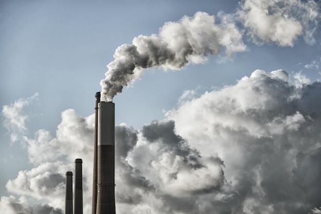 Zanieczyszczenie powietrza. długie rury fabryki, zakładu lub elektrowni dymią i zanieczyszczają powietrze i atmosferę.