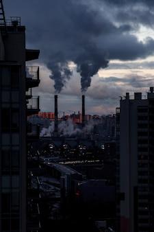 Zanieczyszczenie środowiska i powietrza, koncepcja problemów ekologicznych. dym z kominów fabrycznych na tle szarego pochmurnego nieba. miejski krajobraz.
