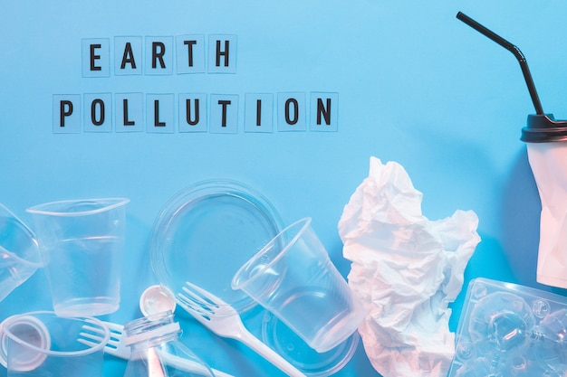 Zanieczyszczenie ziemi. zaśmiecanie plastikiem. problem ekologii. jednorazowa zastawa stołowa na niebiesko