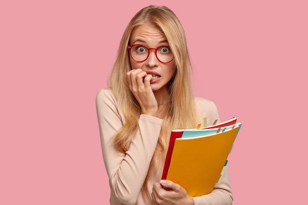 Zaniepokojona blond studentka pozuje na różowej ścianie