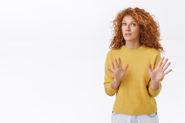Zaniepokojona i zaniepokojona rudowłosa kędzierzawa kobieta uspokaja osobę, mówiąc nie strzelaj, podnosząc ręce, błagając o zatrzymanie, wyglądaj na wystraszoną lub zdenerwowaną, przekonaj kogoś, by upuścił broń, biała ściana