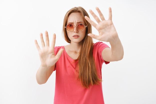 Zaniepokojona i zmartwiona młoda rudowłosa kobieta w okularach przeciwsłonecznych i różowej koszulce zaczyna nerwowo otwierać usta marszcząc brwi unosząc dłonie w pobliżu klatki piersiowej, jakby tkwiła w pudełku, powstrzymując się od niebezpiecznego mężczyzny