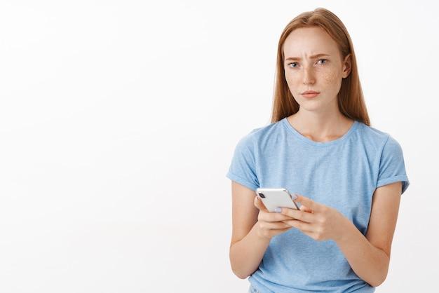 Zaniepokojona kobieta nie może zrozumieć sensu przekazu, wygląda na zakwestionowaną i skupioną zmarszczoną brwi, mrużąc oczy podczas myślenia o ponownym rozważeniu oferty, trzymając smartfon