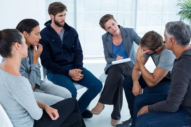 Zaniepokojona kobieta pocieszająca innego w grupie rehabilitacyjnej