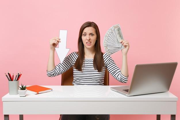 Zaniepokojona kobieta trzyma strzałkę spadku wartości, pakuje dużo dolarów, gotówka pracuje przy białym biurku z laptopem na pc