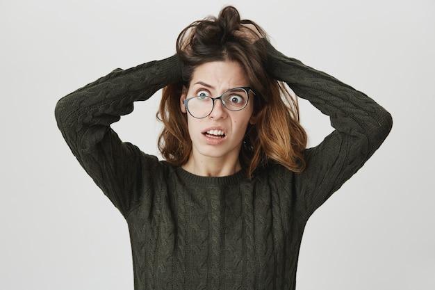 Zaniepokojona kobieta w panice, w przekrzywionych okularach i potarganych włosach