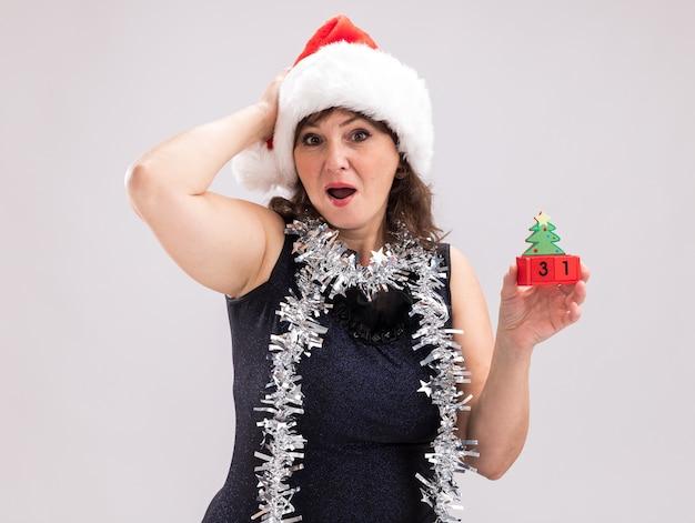 Zaniepokojona kobieta w średnim wieku nosząca santa hat i blichtrową girlandę wokół szyi trzymająca choinkę zabawkę z datą trzymającą rękę na głowie patrząc na kamerę na białym tle