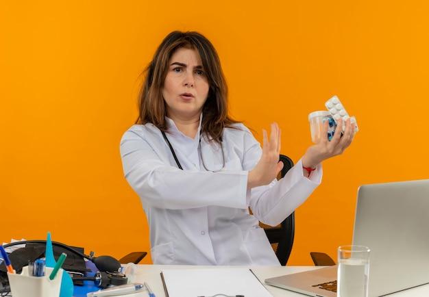 Zaniepokojona kobieta w średnim wieku ubrana w szlafrok medyczny ze stetoskopem siedząca przy biurku na laptopie z narzędziami medycznymi trzymającymi pigułki i pokazująca gest stop na odizolowanej pomarańczowej ścianie