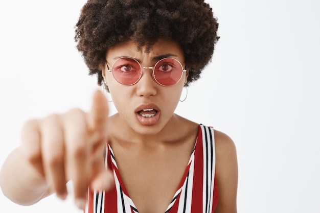 Zaniepokojona kobieta wpatrująca się w coś zagmatwanego, wskazująca podczas przesłuchania i nieświadoma, otwierająca usta i marszcząca brwi, czująca intensywność i niepewność, co widzi