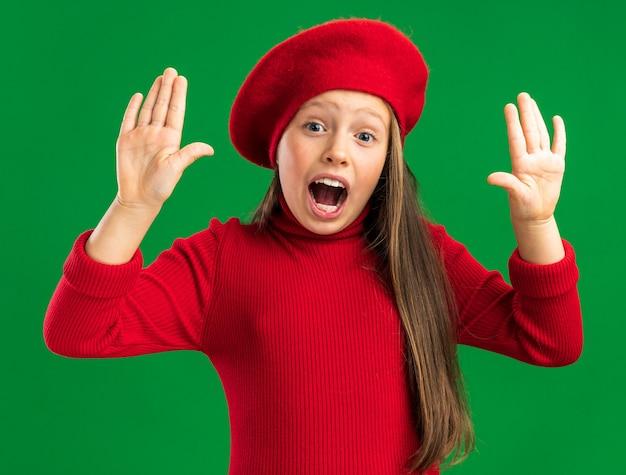 Zaniepokojona mała blondynka ubrana w czerwony beret, trzymająca puste ręce w powietrzu na zielonej ścianie