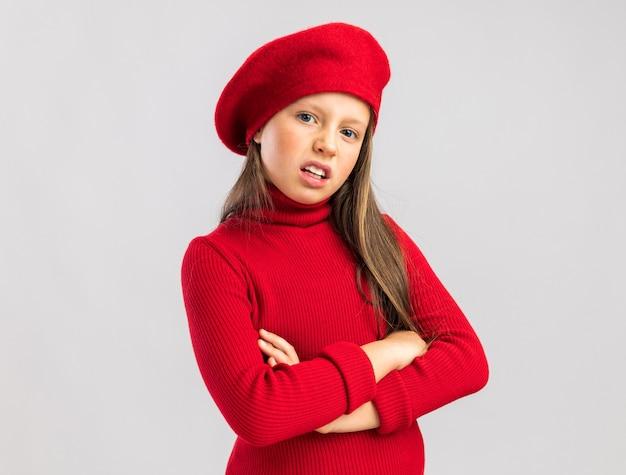Zaniepokojona mała blondynka ubrana w czerwony beret trzymający skrzyżowane ręce patrząc na przód na białej ścianie z miejscem na kopię