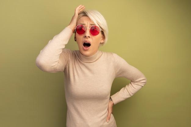 Zaniepokojona młoda blondynka nosi okulary przeciwsłoneczne, kładąc dłoń na głowie, trzymając drugą w talii, patrząc z boku