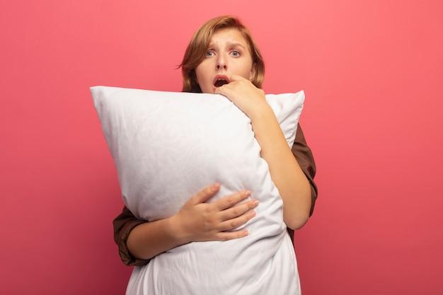 Zaniepokojona młoda blondynka przytula poduszkę patrząc na przód odizolowaną na różowej ścianie z miejscem na kopię