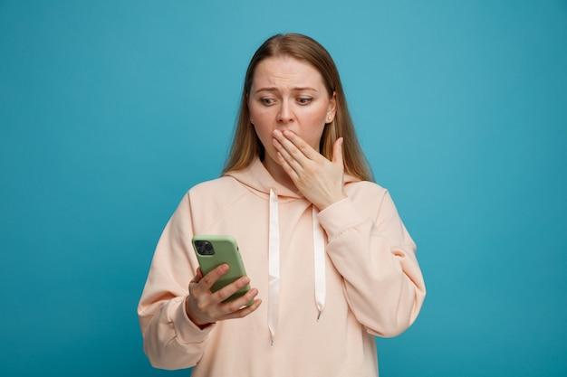 Zaniepokojona młoda blondynka trzyma i patrząc na telefon komórkowy robi gest ups